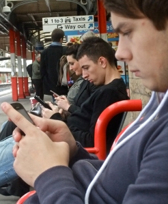 Three people sat immersed in their mobile communications devices, Lancaster railway station, 11/10/11