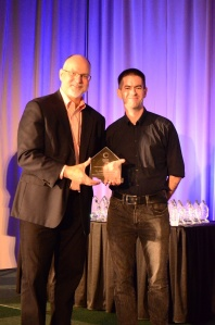 Drew Whitworth, MA: DTCE Programme Director, receiving the award from Blackboard's President (Academic Platforms), Ray Henderson